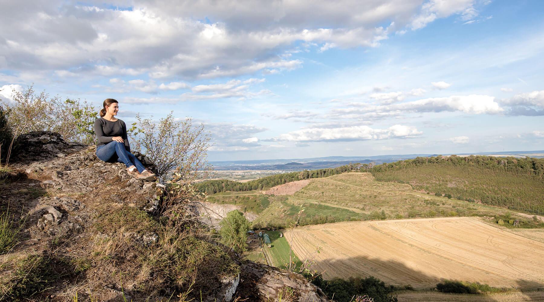 Vulkanpark Ettringer Bellerberg Eine Frau sitzt auf dem Gipfel des Ettringer Bellerbergs