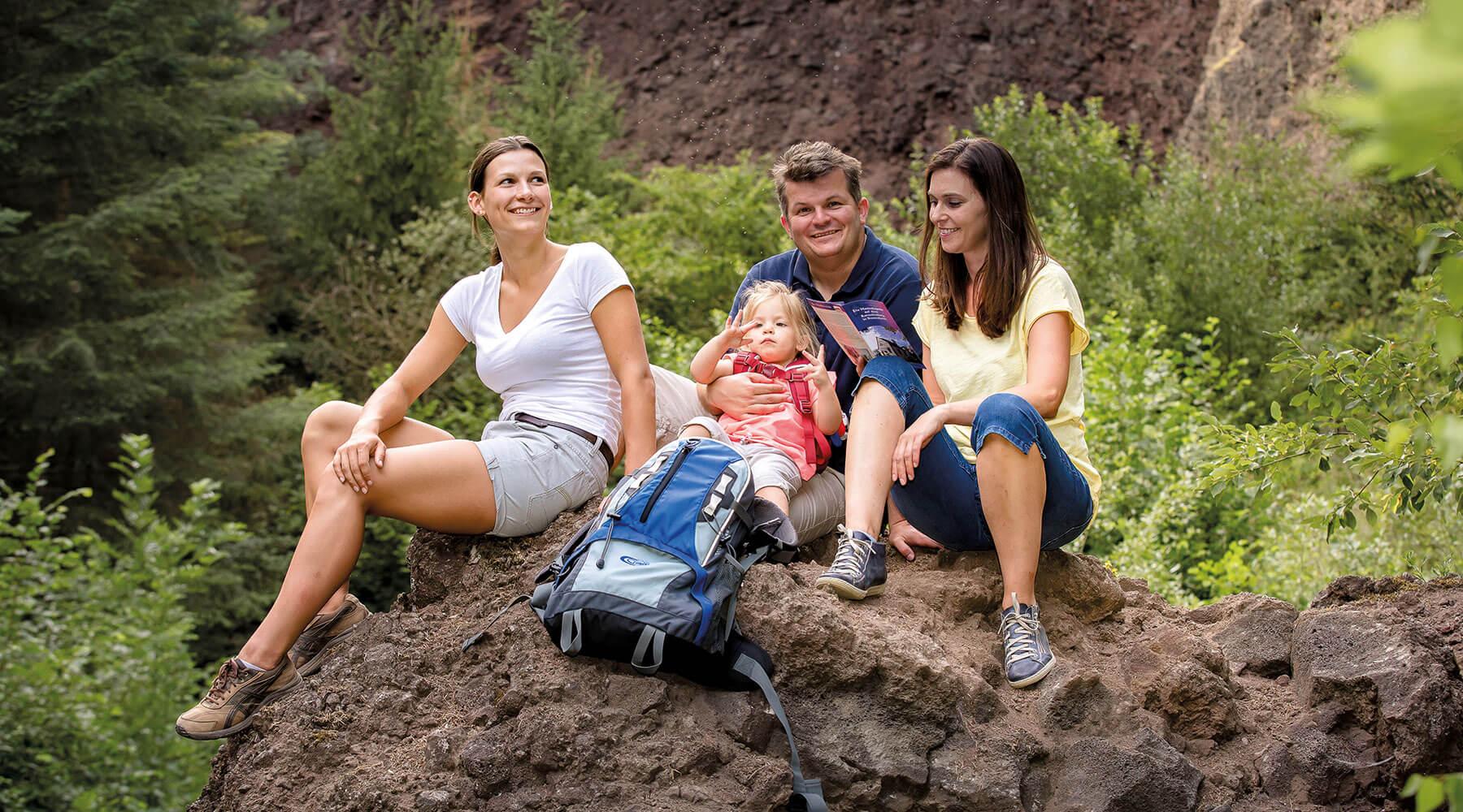 Vulkanpark Karmelenberg 4 Personen und ein Kind sitzen auf einem großen Stein am Karmelenberg
