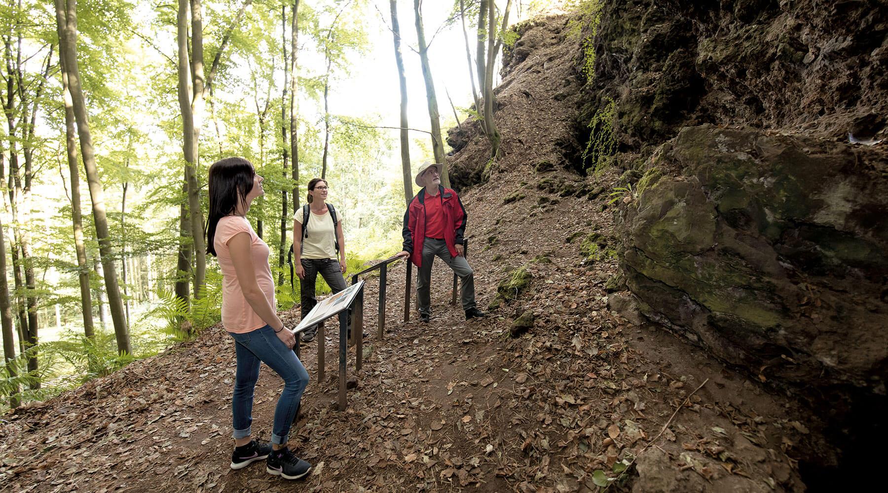 Vulkanpark Kottenheimer Büden Drei Personen betrachten eine Gesteinswand am Kottenheimer Büden