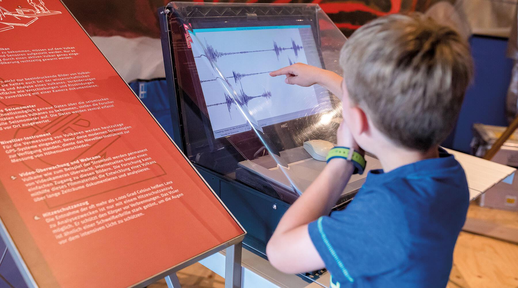 Vulkanpark, Lava-Dome. Ein Kind schaut auf einen Seismograph.