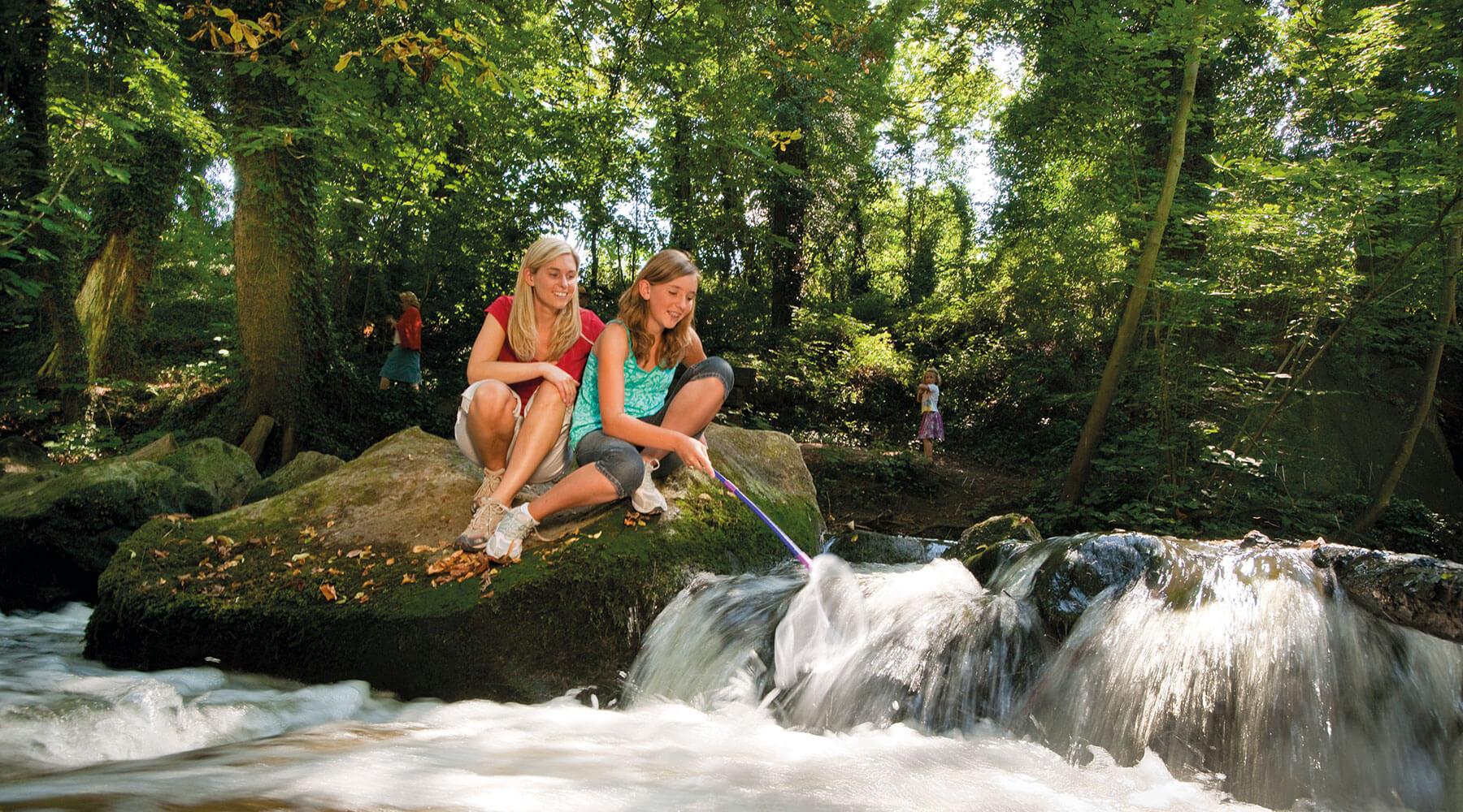 Vulkanpark Rauscherpark Zwei Frauen sitzen auf einem Stein direkt an der Nette