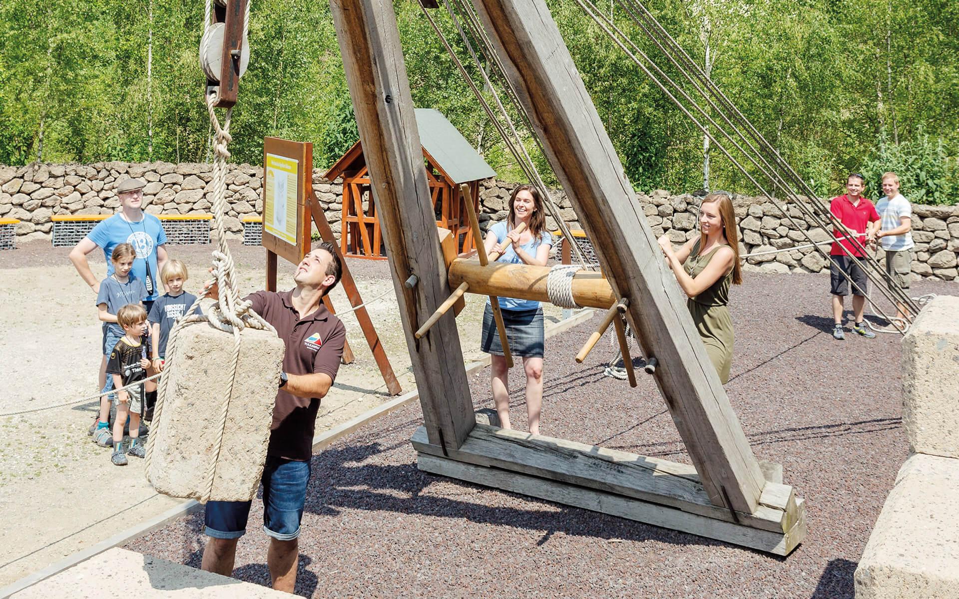 Vulkanpark, Römerbergwerk Meurin. Gemeinsam mit einem Gästeführer nehmen Besucher den antiken Kran in Betrieb.
