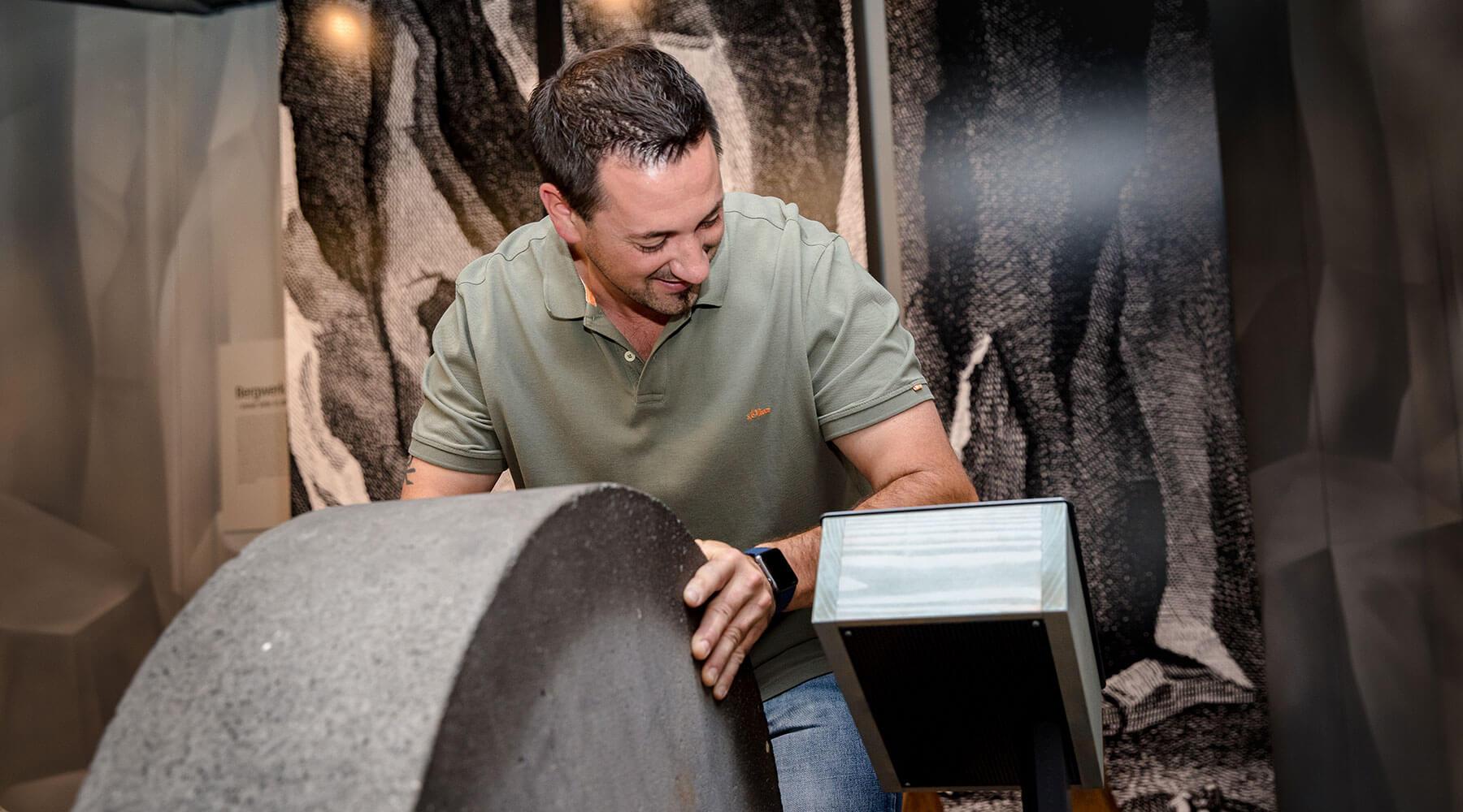 Vulkanpark, Erlebniswelten Grubenfeld. Ein Mann probiert sich an der Steinrollsimulation.