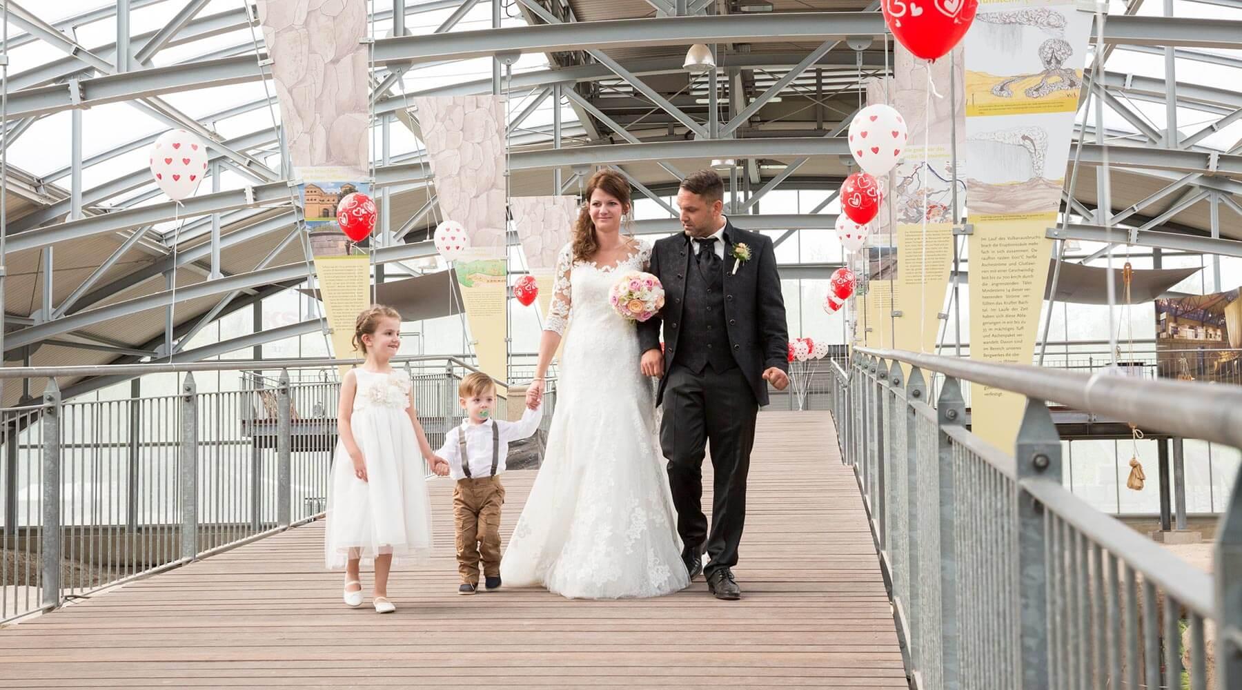Vulkanpark, Römerbergwerk Meurin. Ein Brautpaar zieht zusammen mir ihren Kinder über den breiten Holzsteg ein.
