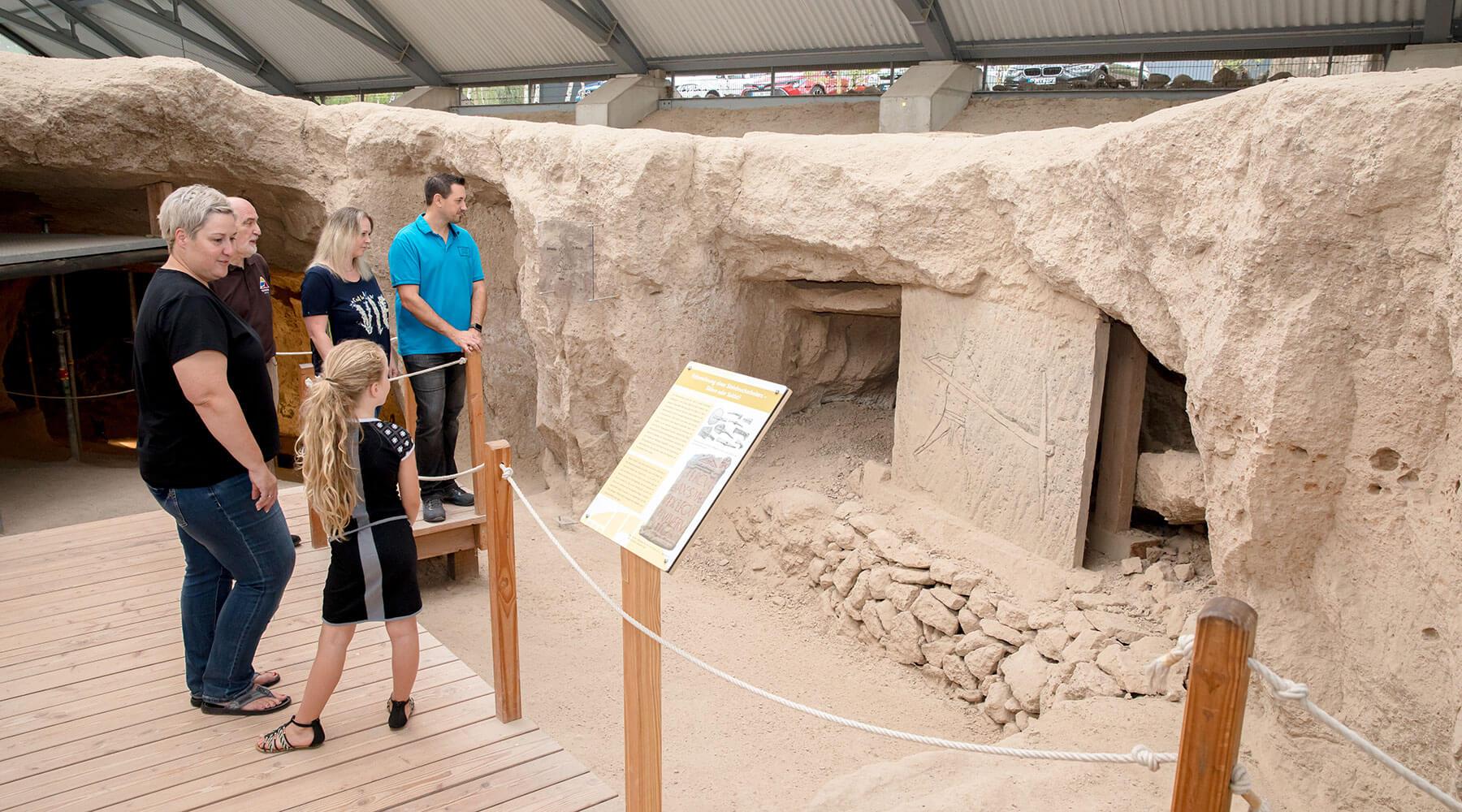 Vulkanpark, Römerbergwerk Meurin. Gästeführer erläutert Besuchern die Felszeichnung.